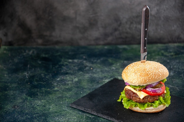 Close up shot of knife in delicious sandwich on the left side on black tray on isolated blurred surface with free space