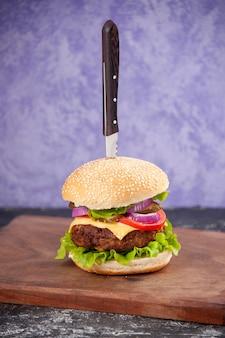 Immagine ravvicinata di coltello in gustoso panino di carne su tagliere di legno su superficie di ghiaccio isolata con spazio libero