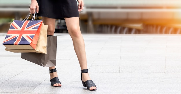 Close up shot of lady's  leg carrying colorful shopping bags while waiting the taxi.