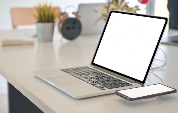 Close-up shot of laptop and smartphone mockup a blank screen on a desk.
