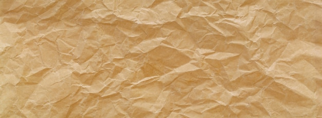 Close up shot of light brown crumpled recycled paper texture banner background