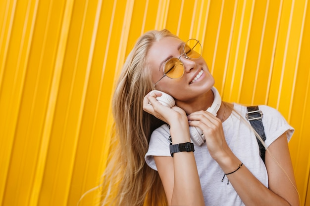 Close-up shot of lovable european woman listening music and laughing.