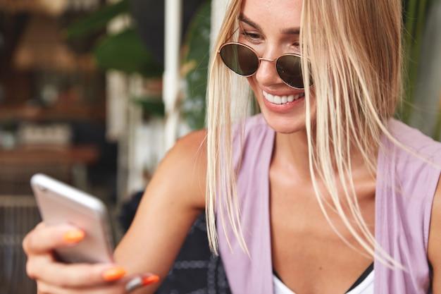 Immagine ravvicinata di bella donna felice in occhiali da sole con il telefono