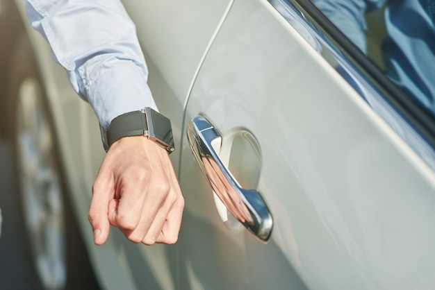 Close up shot of a male hand with smartwatch man going to open the car while standing outdoors