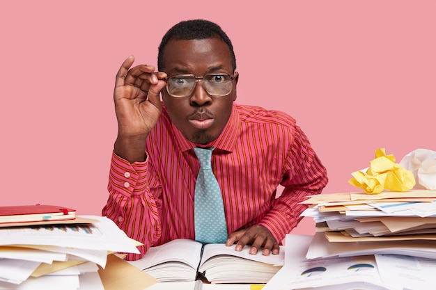 Close up shot of male wonk looks scrupulously, keeps hand on rim of spectacles, dressed in formalwear, sits at desktop, reads literature