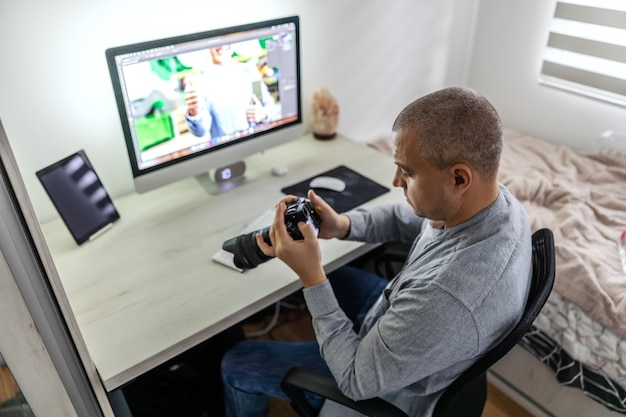A close-up shot of a man employed in a media agency who controls and monitoring photos with the most modern camera