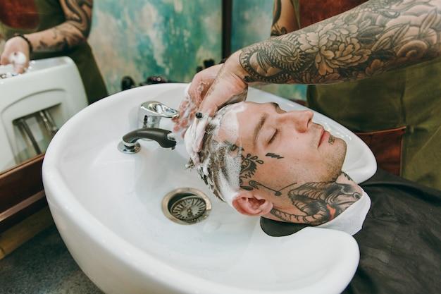 Immagine ravvicinata dell'uomo che ottiene taglio di capelli alla moda al negozio di barbiere. l'hairstylist maschile in tatuaggi che serve il cliente, lavando la testa