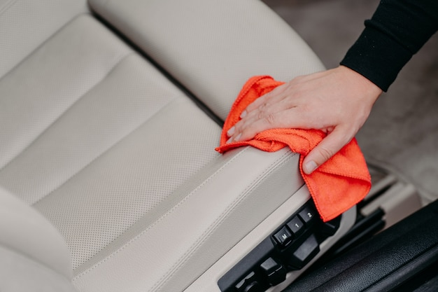 Close up shot of mans hand wipes car seat with microfiber cloth