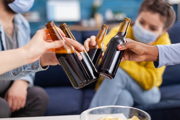 Close up shot of mixed race friends clinking beer bottles hanging out keeping social distancing having fun in apartment linving room during global pandemic. conceptual image.