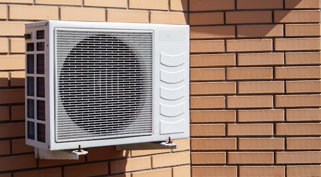Close-up shot of a modern climate control unit against the background of a brick wall of the facade of a house outside. air conditioner on the wall with space for text. air compressor.