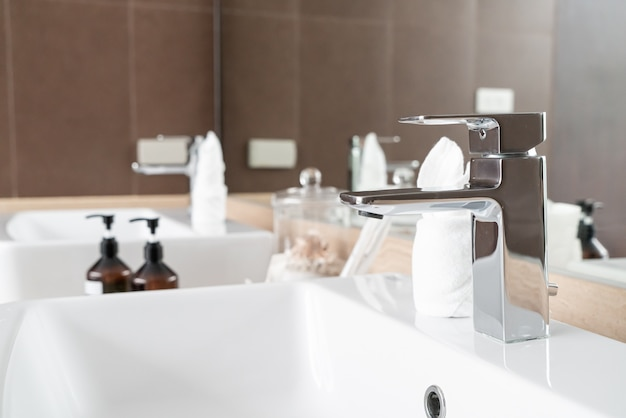 Close up shot of modern metallic faucet in bathroom