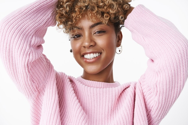 Close-up shot of modern stylish dark-skinned woman with pierced nose and earrings holding hands on curly hair and smiling joyfully wearing trendy pink sweater, posing delighted and carefree