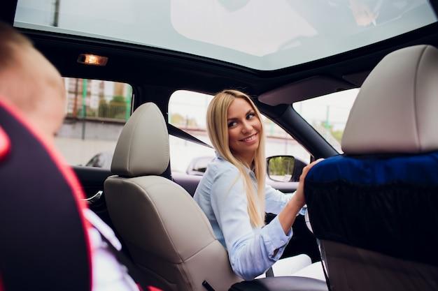 車を運転しているクローズアップショットの母、座屈したシートベルト。後部座席の息子。親指を立てる家族
