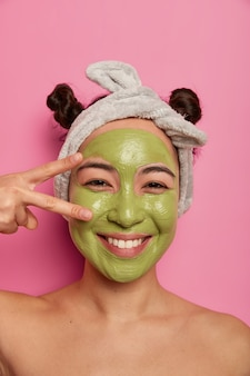 Close up shot of natural asian woman has fun during beauty procedures, makes peace sign over eye, applies green purifying facial mask, cleanses skin, stands with naked body isolated on pink wall