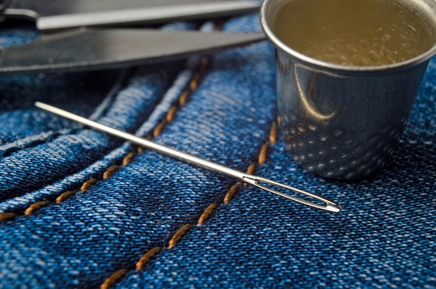Close-up shot of needle with thread on jeans material. close-up.