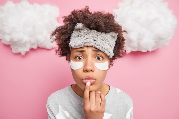 Close up shot of nervous afro american woman keeps finger on folded lips dressed in nightwear wears sleepmask on forehead isolated over pink wall white clouds above
