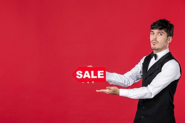 Immagine ravvicinata di cameriere ragazzo nervoso in un'uniforme con farfalla sul collo che mostra l'icona di vendita che punta qualcosa sul lato destro su sfondo rosso isolato