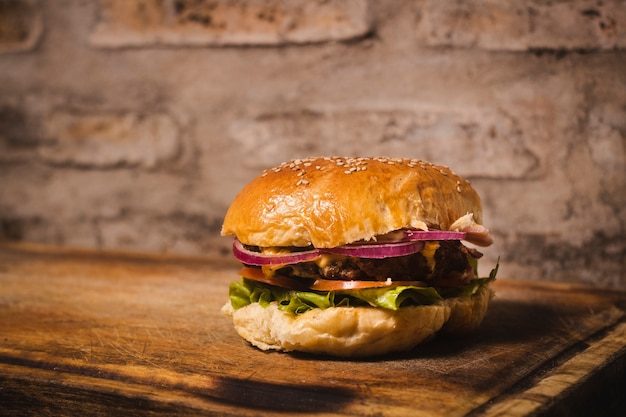 Close up shot of a nice looking hamburguer on a wooden board