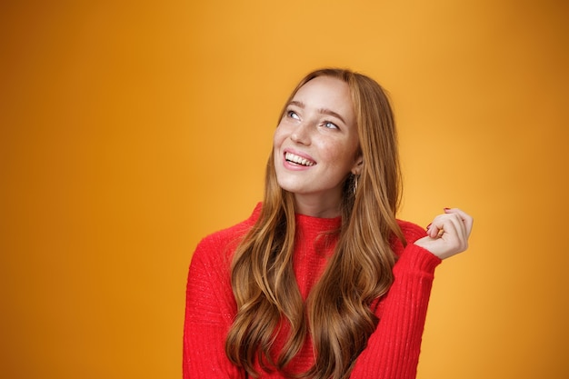 Primo piano di una femmina europea nostalgica carina e sensuale dall'aspetto amichevole con bei ricordi carini guardando l'angolo in alto a sinistra sognante e felice, immaginando e immaginando il desiderio sul muro arancione