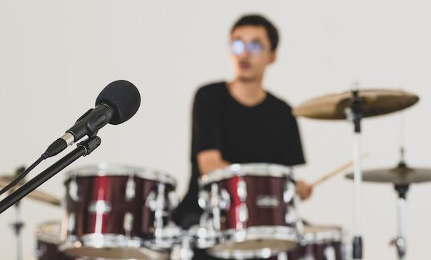 若い10代のドラマーがバックグラウンドで演奏している黒いプロのマイクのクローズアップショット。白い背景でドラムを演奏する若いミュージシャンとマイクで選択的な焦点