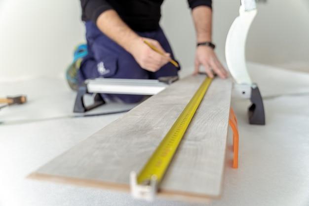 바닥 설치를 수행하기 위해 나무 판자를 측정하는 목수의 총을 닫습니다