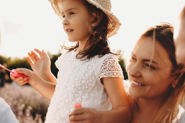 외부 그녀의 딸과 함께 연주 사랑스러운 젊은 어머니의 총을 닫습니다. 일몰에 대 한 야외 그녀의 부모와 함께 재미 모자를 쓰고 달콤한 작은 소녀.