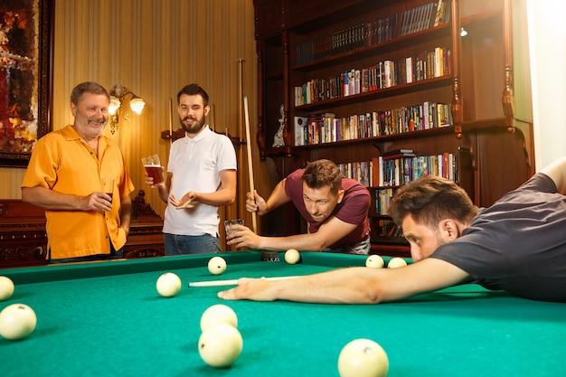 ビリヤードをしている男性のクローズアップショット。白人モデルは、ボールのキューで慎重かつ精力的に狙っています。ゲームのコンセプト
