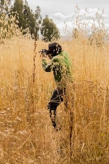 乾燥した植物の黄金色のフィールドで写真を撮るカメラを持つ男のクローズアップショット
