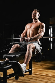 Снимок крупным планом мужчины с голым торсом, выполняющего упражнения для мышц спины на тренажере в спортивном зале