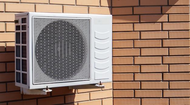 외부 집 정면의 벽돌 벽 배경에 대한 현대적인 기후 제어 장치의 클로즈업 샷. 텍스트를 위한 공간이 있는 벽에 에어컨. 공기 압축기.