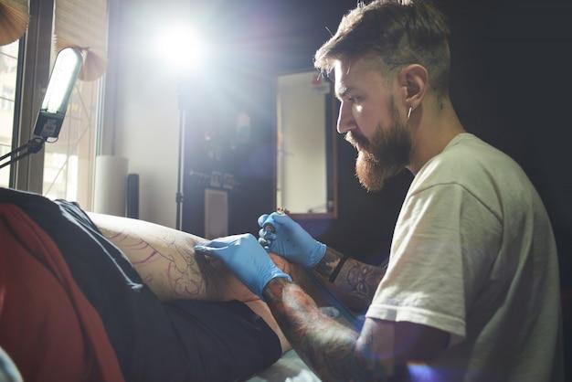 Съемка крупным планом профессионального татуированного бородатого художника татуировки клиента мужчине в салоне