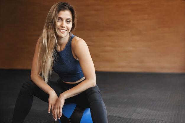 Activewear를 입고 웃는 sportswoman의 근접 촬영 의학 공을 앉는 다.