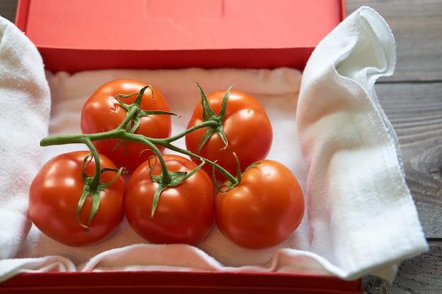 Крупным планом вкусные органические свежие ветки красных помидоров в красном картоне