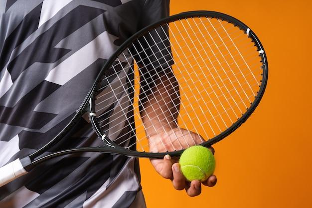 テニスラケットとボールでテニスプレーヤーの手のショットをクローズアップ