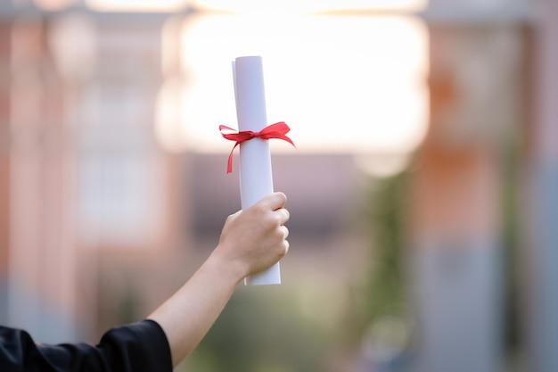 Крупный план выпускника университета, имеющего диплом, который показывает и празднует успехи в учебе в день поступления в колледж. сток фото