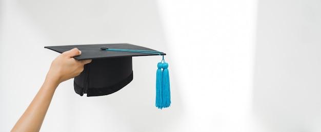 Крупным планом - выпускник университета в выпускном платье с дипломом о высшем образовании, участвующий в шоу и празднующий успех в день поступления в колледж. сток фото