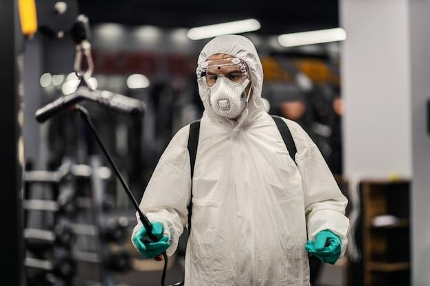 고글과 마스크를 쓴 보호복을 입은 걱정스러운 남성의 클로즈업 샷. 그는 체육관에서 코로나바이러스를 이기기 위해 최선을 다했습니다. 코로나19 예방, 대유행 상황, 사회적 거리두기, 뉴노멀