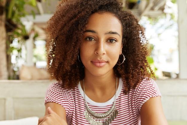 自信に満ちた表情で愛らしい黒肌の女性のクローズアップショット、巻き毛、何かについて熟考しています。アフリカ系アメリカ人の女性は、カフェのインテリアに対して残りがあります。