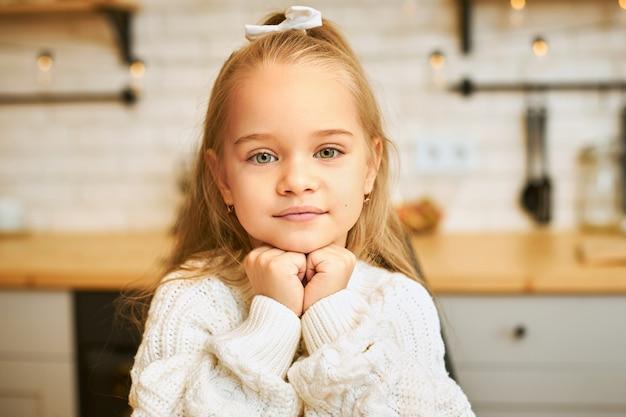 台所でポーズをとって笑顔で彼女のあごの下で手をつないで緑の目と長い緩い髪の愛らしい少女のクローズアップショット