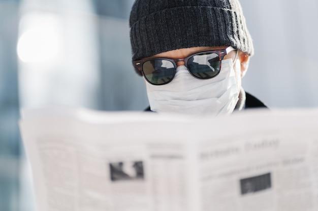 成人男性のショットを閉じる、サングラス、帽子、滅菌医療用マスクを着用、新聞を読む、世界の状況に関するニュースを見つける、コロナウイルスの広がり、背景をぼかした写真に対する屋外ポーズ