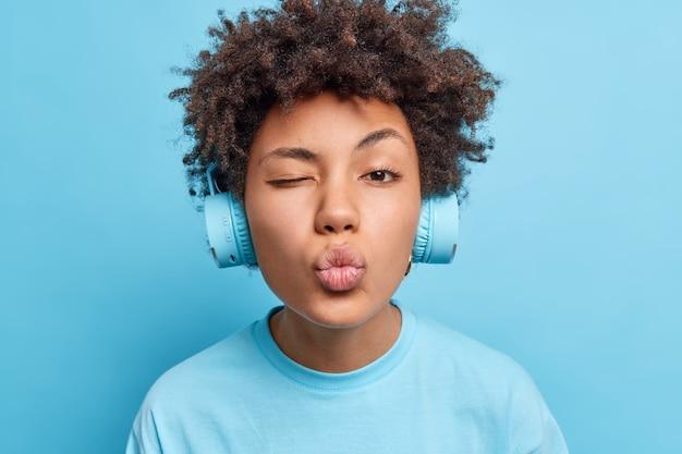 Крупным планом ласковая симпатичная афроамериканка подмигивает глазам, держит округлые губы, наслаждается прослушиванием аудиодорожки через наушники, небрежно одетые, изолированные на синей стене. концепция хобби