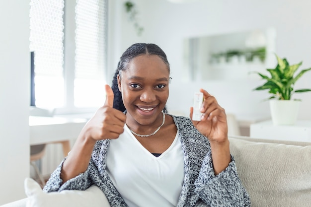 ネガティブテストデバイスを持っているアフリカ系アメリカ人の女性の手のクローズアップショット。彼女の陰性コロナウイルスを示す幸せな若い女性-covid-19迅速なテスト。焦点はテストにあります。コロナウイルス