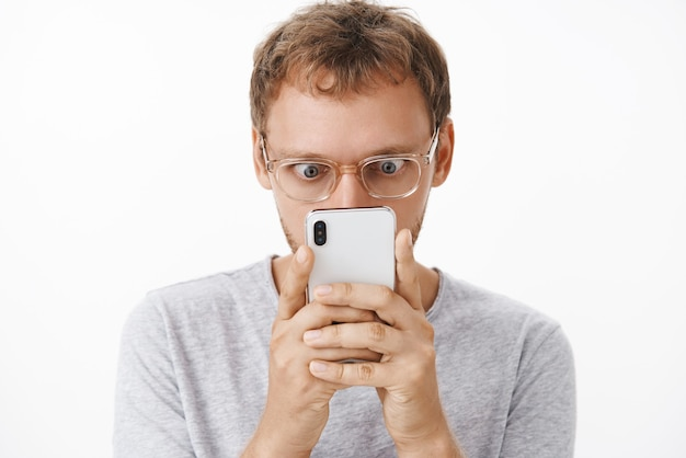 Крупным планом веселый и развлеченный мужчина-компьютерщик в очках, держащий смартфон близко к лицу, вылезающие глаза и заинтригованный смотрящий на экран устройства, читающий шокирующее интересное сообщение над белой стеной
