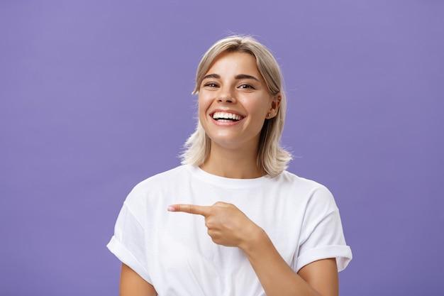 Снимок крупным планом удивленной, счастливой и веселой симпатичной общительной женщины со светлыми волосами и красивой улыбкой, улыбающейся, указывая указательным пальцем влево