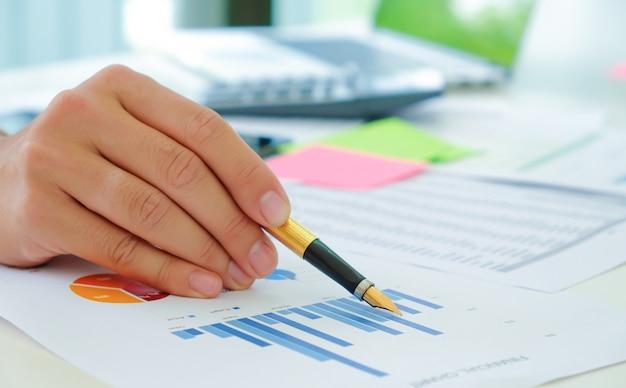 Съемка крупным планом аналитики используют ручку, чтобы указать на график, чтобы оценить ситуацию на фондовом рынке, который колеблется.