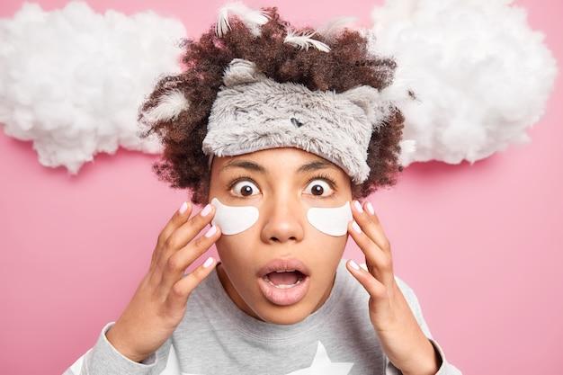 Снимок крупным планом изумленной эмоциональной афроамериканской женщины, накладывающей пластыри под глаза, смотрит в камеру, носит мягкую повязку на глаза, проходит процедуры по уходу за кожей, позирует над розовыми облаками на стене выше