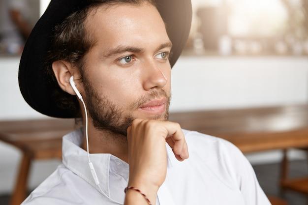 Крупным планом - привлекательный и стильный мужчина с задумчивой бородой, который слушает музыку в интернете в белых наушниках и использует какое-то электронное устройство, ожидая свою девушку в кафе