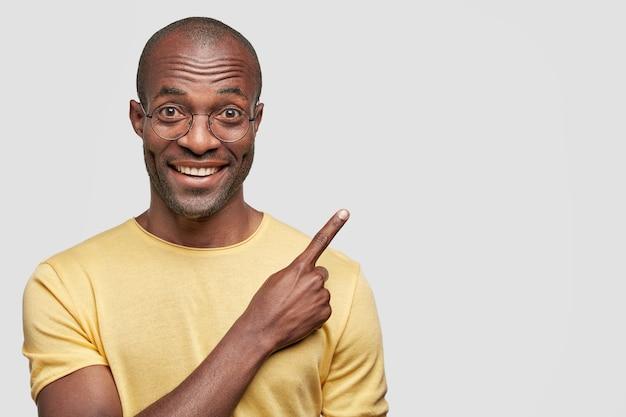 노란색 캐주얼 티셔츠를 입은 매력적인 쾌활한 젊은 어두운 피부 아프리카 계 미국인 남성의 총을 닫습니다