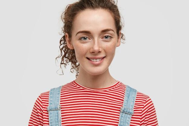 곱슬 머리를 가진 매력적인 주근깨가있는 여자의 총을 닫고 긍정적으로 미소 짓고 좋은 분위기에 있습니다.