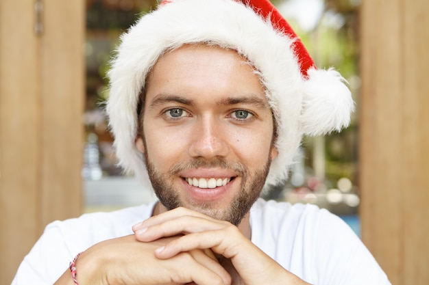 サンタクロースの帽子をかぶってカメラを見て元気に笑って、熱帯の国で幸せな休暇を楽しみながら新年のパーティーを待っている魅力的な無精ひげを生やした若い男のショットをクローズアップ